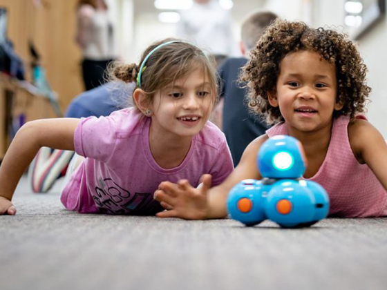 Children playing with a robot to learn more about technology.