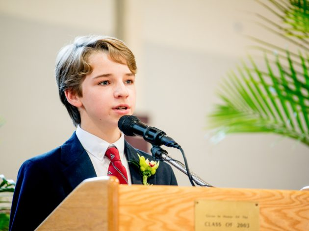 A student speaking at a podium at graduation.