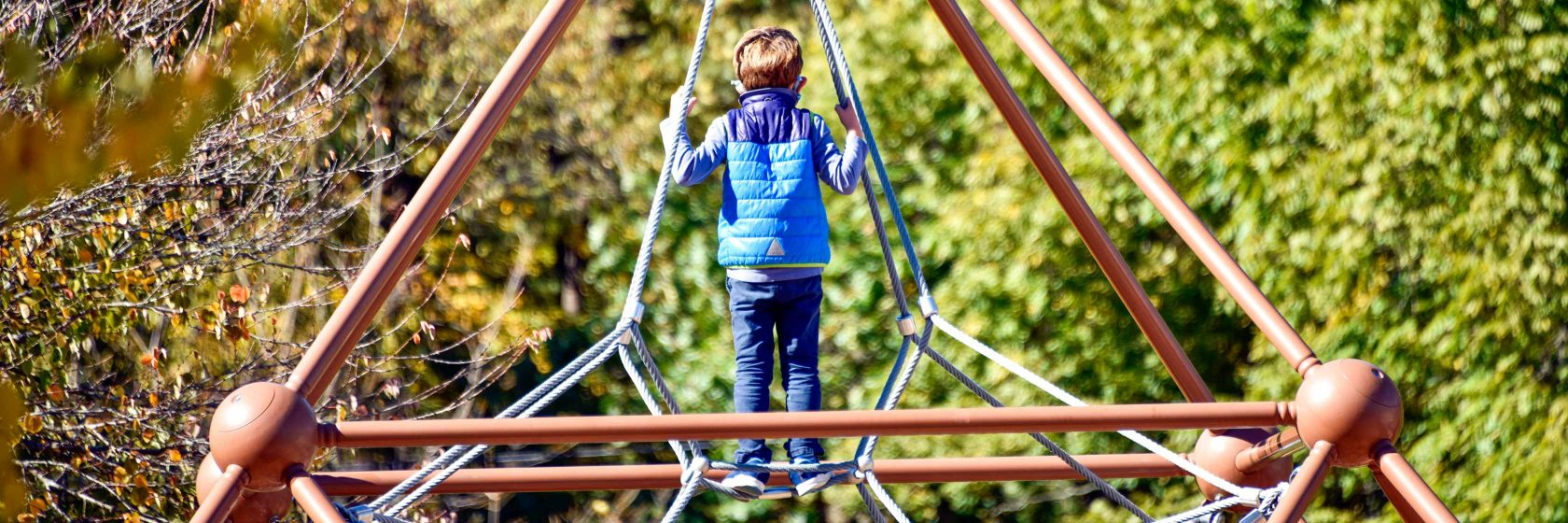 A student on a climbing gym at the school playground.