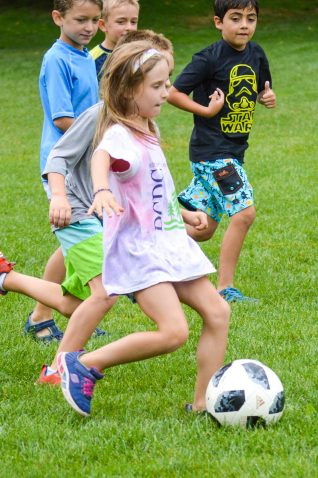 A girl playing soccer with other campers.