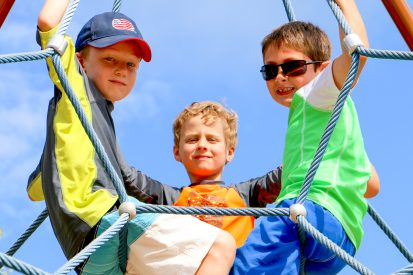 Campers sitting on climbing ropes.