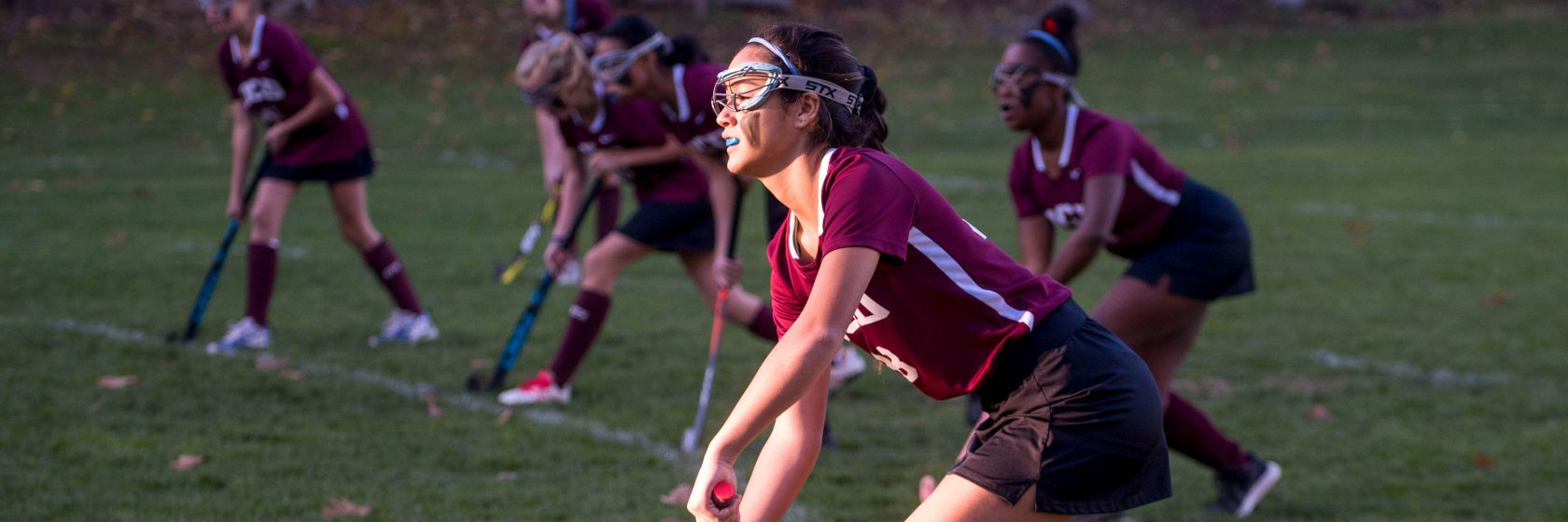 A student playing field hockey.