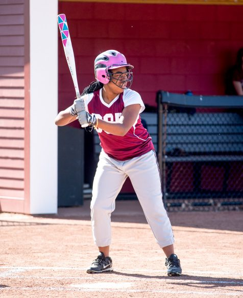 A student standing at home base ready to play softball.