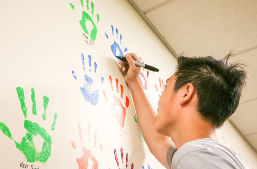 A student signing their hand print and their name on a wall.