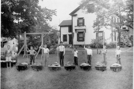 Students pose with the kayaks they made in woodshop in the 1940s.