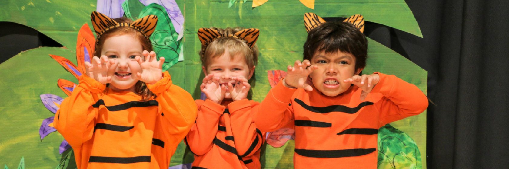 A group of children dressed as tigers posing on stage.