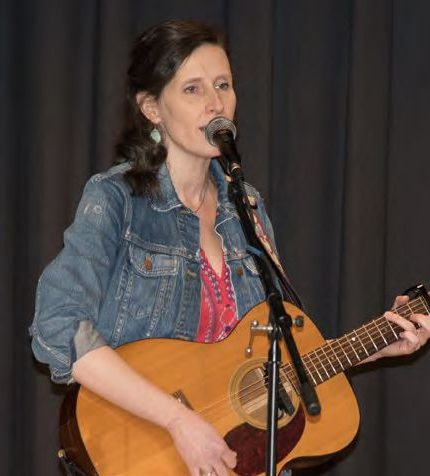 Edie Carey singing and playing the guitar.