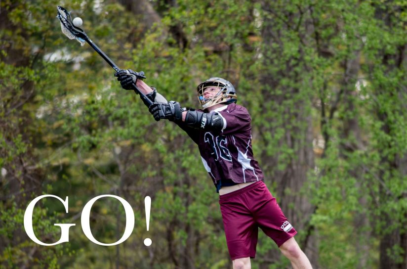 A student catching a lacrosse ball.