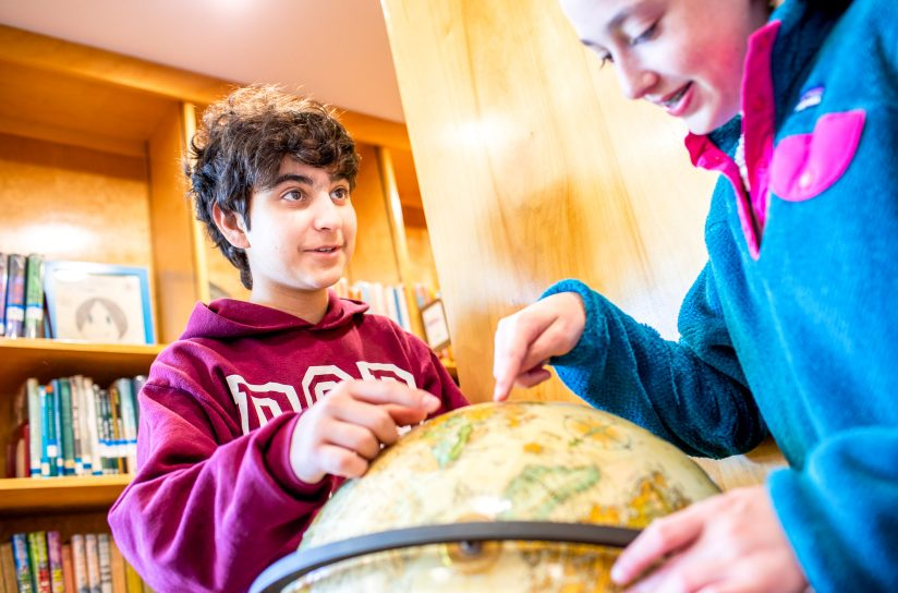 Two students examining a globe.