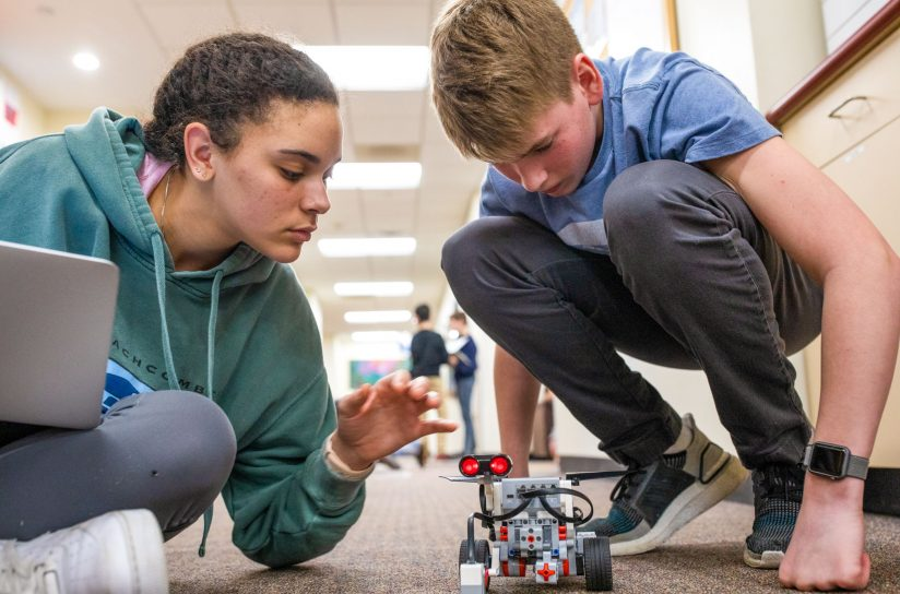 Two students working with a robotic lego car.