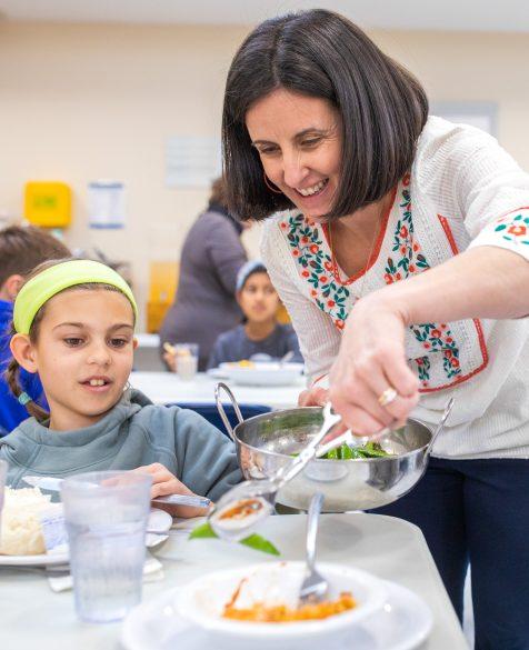 A teacher serving a salad to a student.