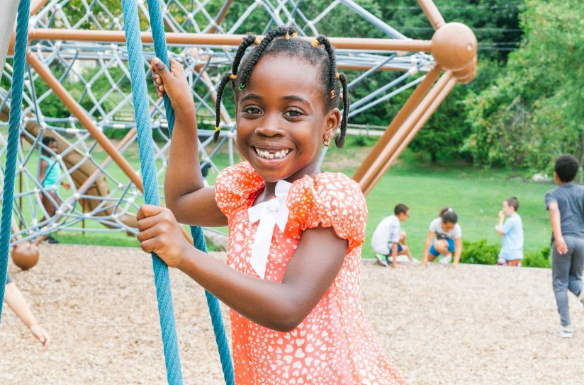 A student smiling while playing on a playground.