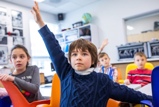 A student raising their hand in class.