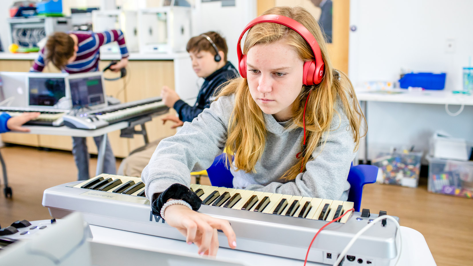 A student playing music on an electronic keyboard.