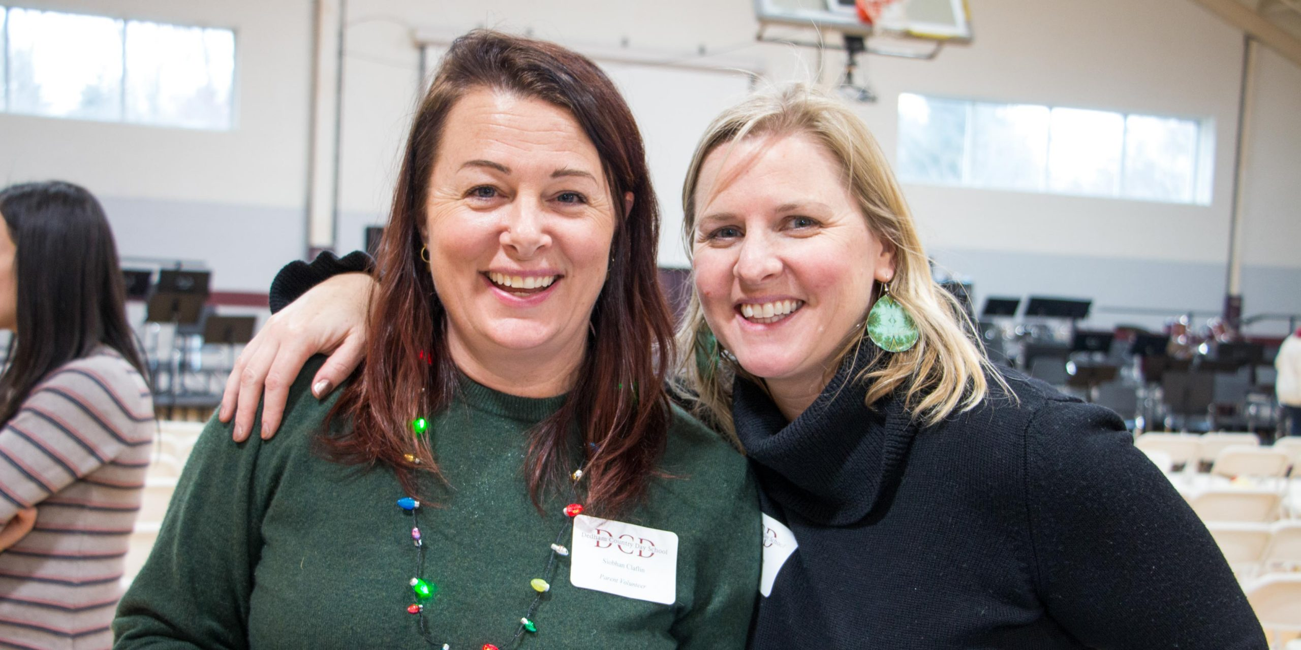 Two parents smiling at the camera at a parent volunteer event.