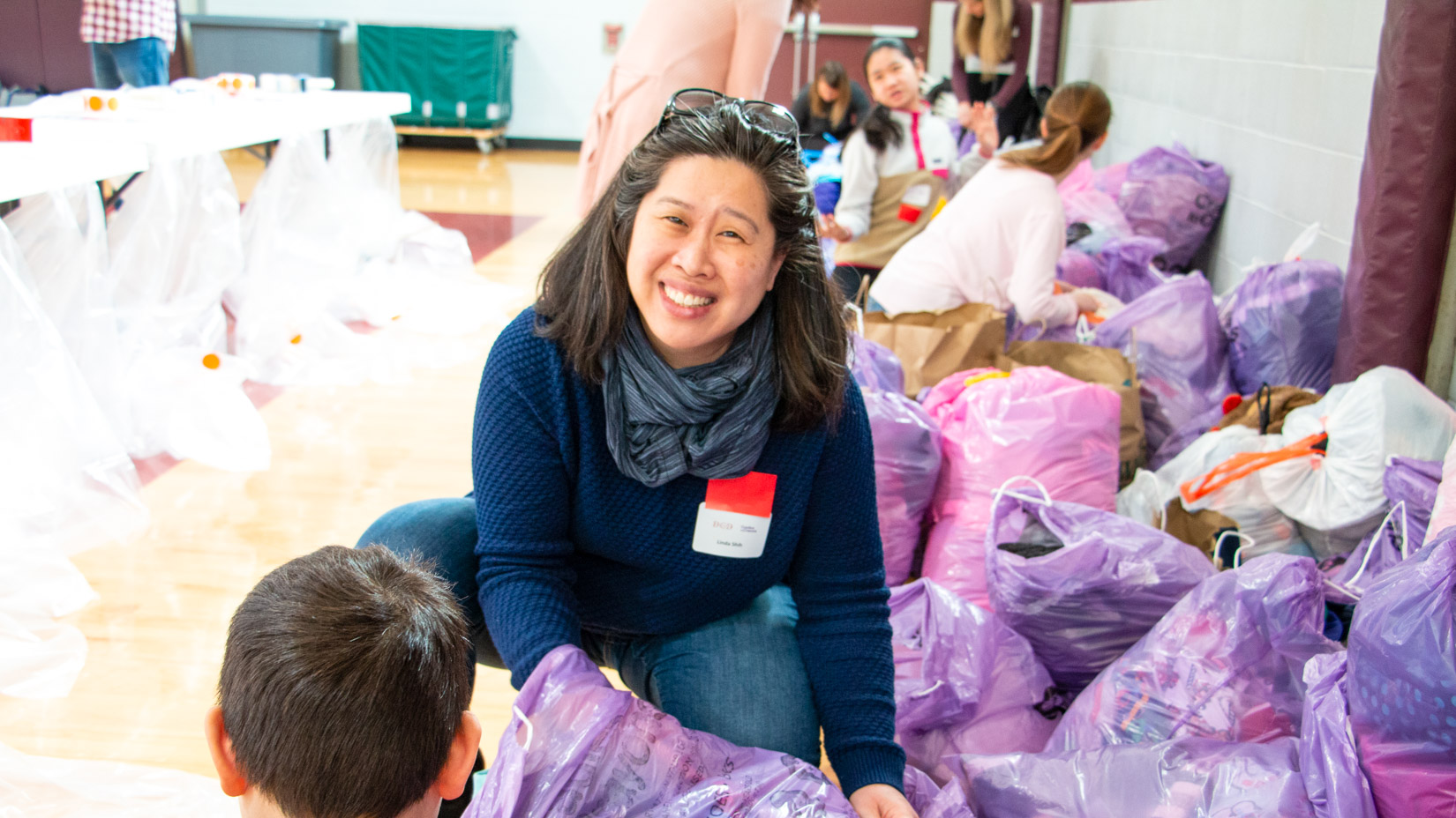 A parent working with donated items at an event.