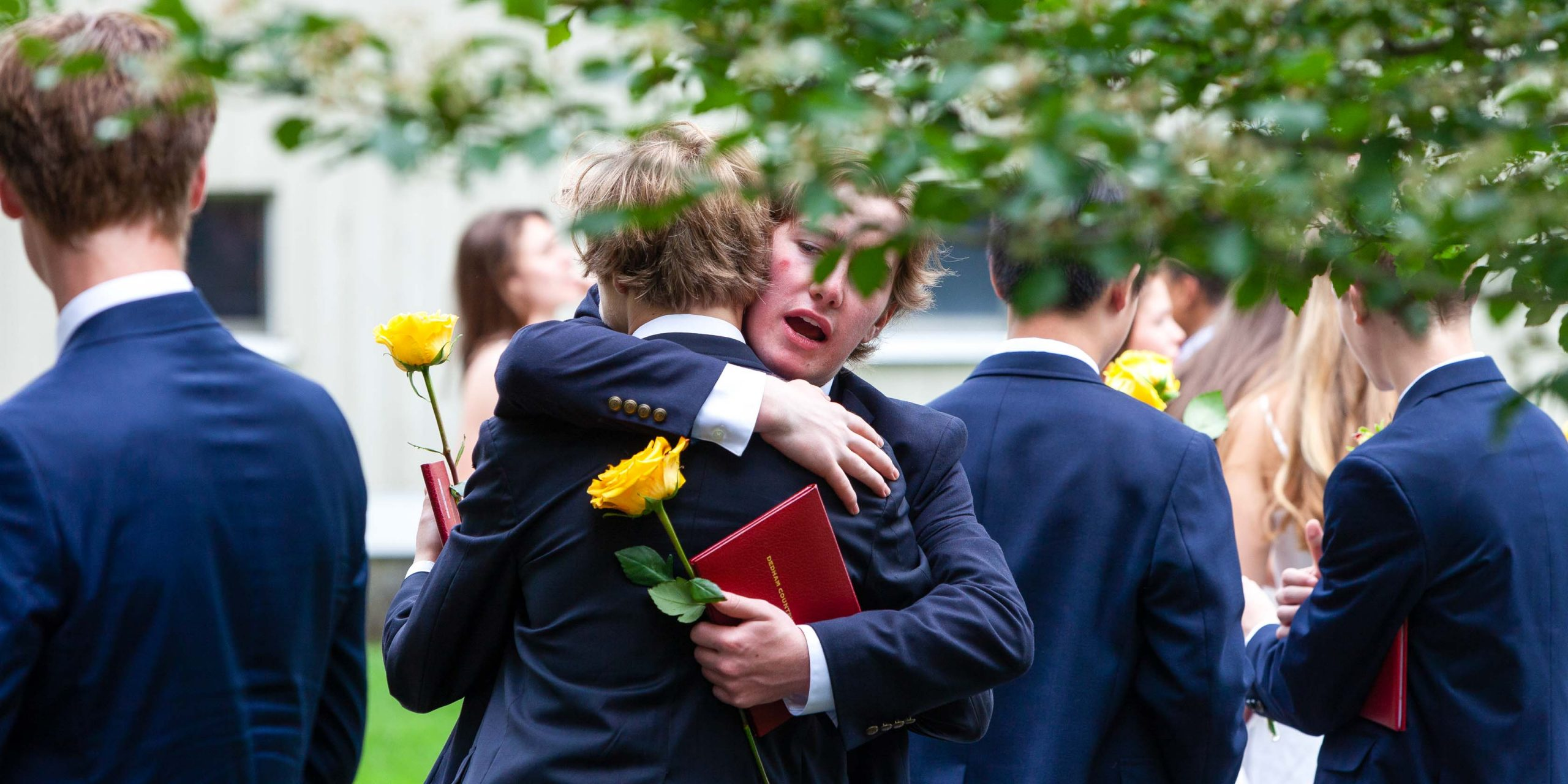 Students hugging after the graduation ceremony.