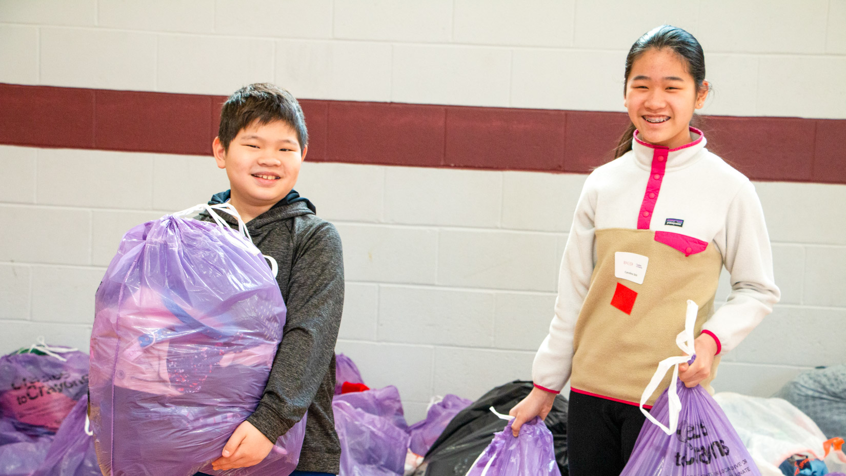 Students with clothes donation bags.