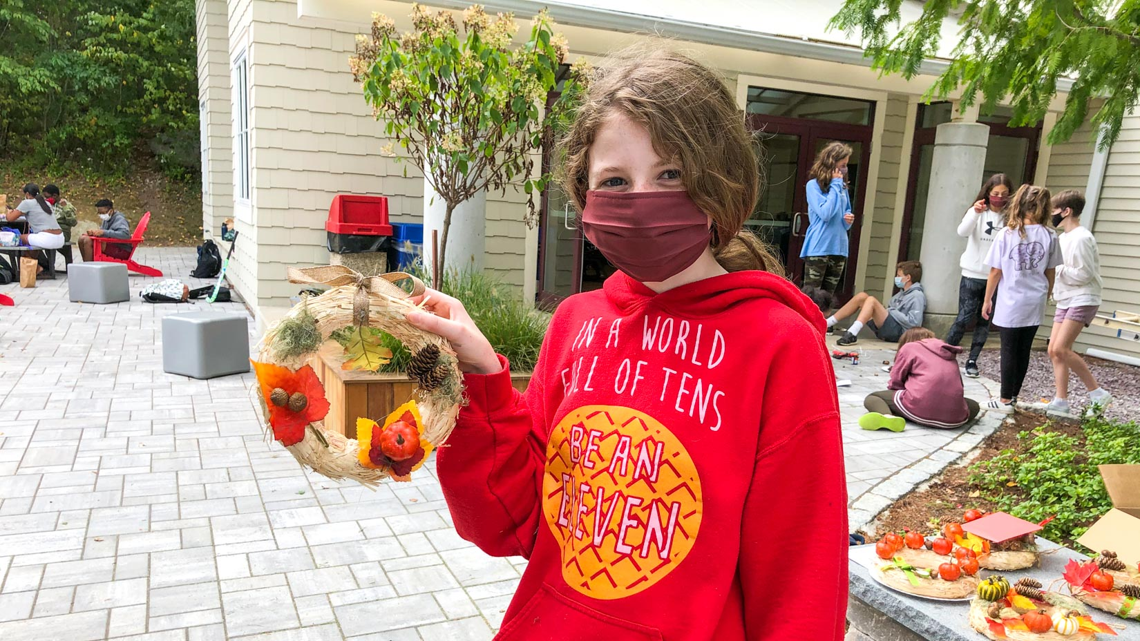 A student in a mask holding up a wreath.