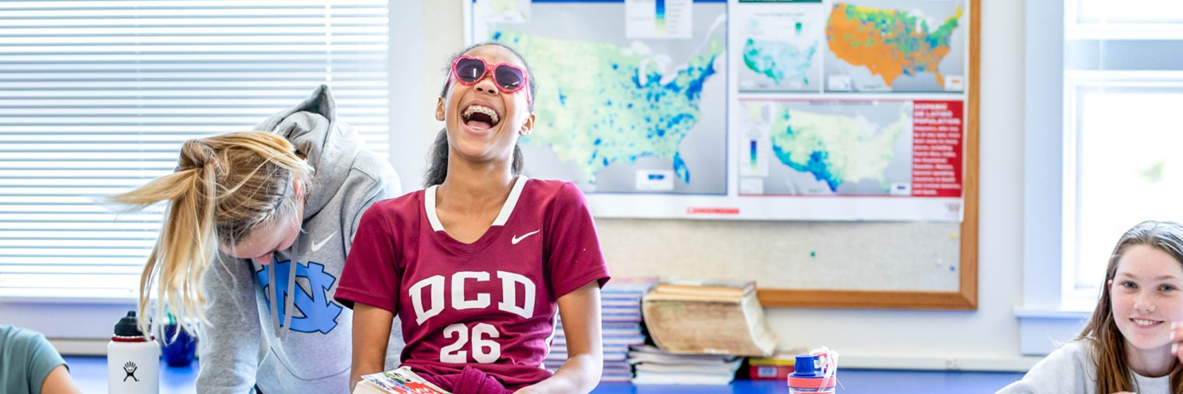 Students smiling and laughing in a classroom.