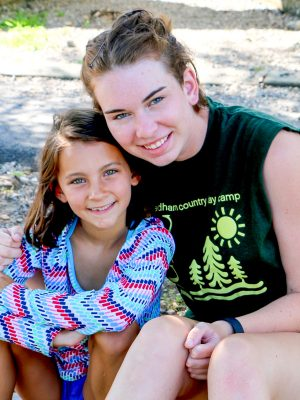 A camper and a counselor posing and smiling together.