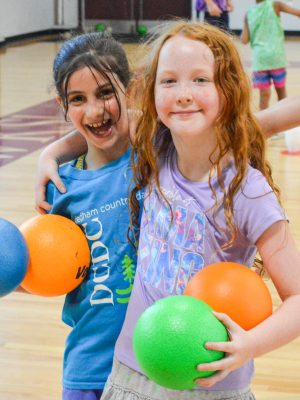 Campers smiling while playing dodgeball.