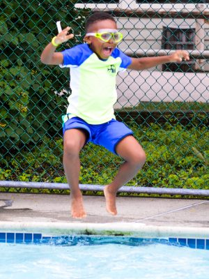 A young camper jumping into the pool.