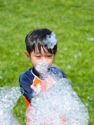 A young camper playing with bubbles.