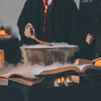A person holding a wand over a steaming cauldron like Harry Potter.