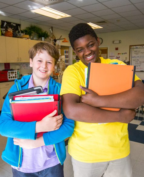 Two students standing with their books and smiling in a classroom.