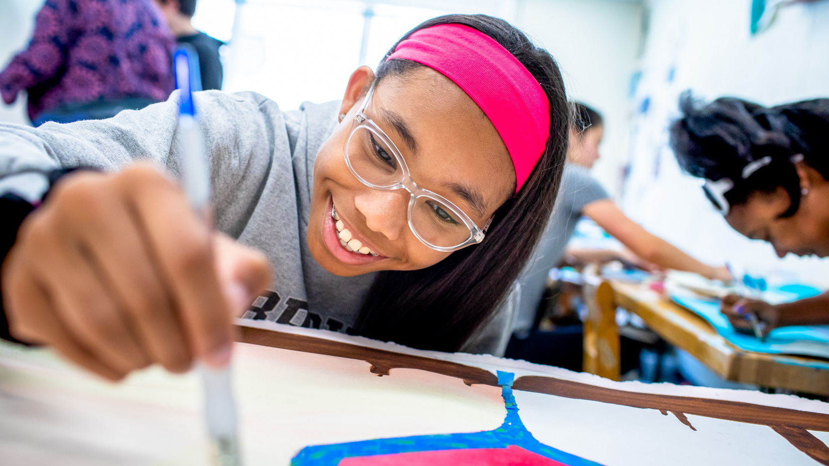 A student smiling while drawing a picture.
