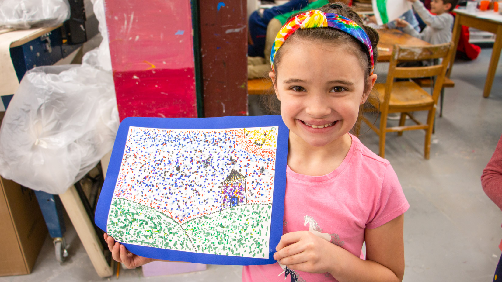 A student smiling with their drawing.