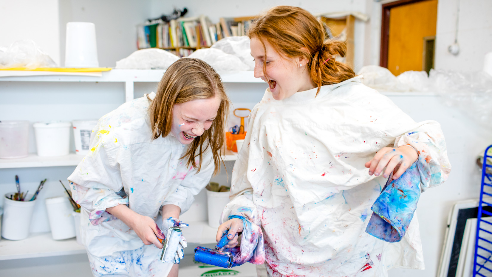 Two students working on an art project together and laughing.