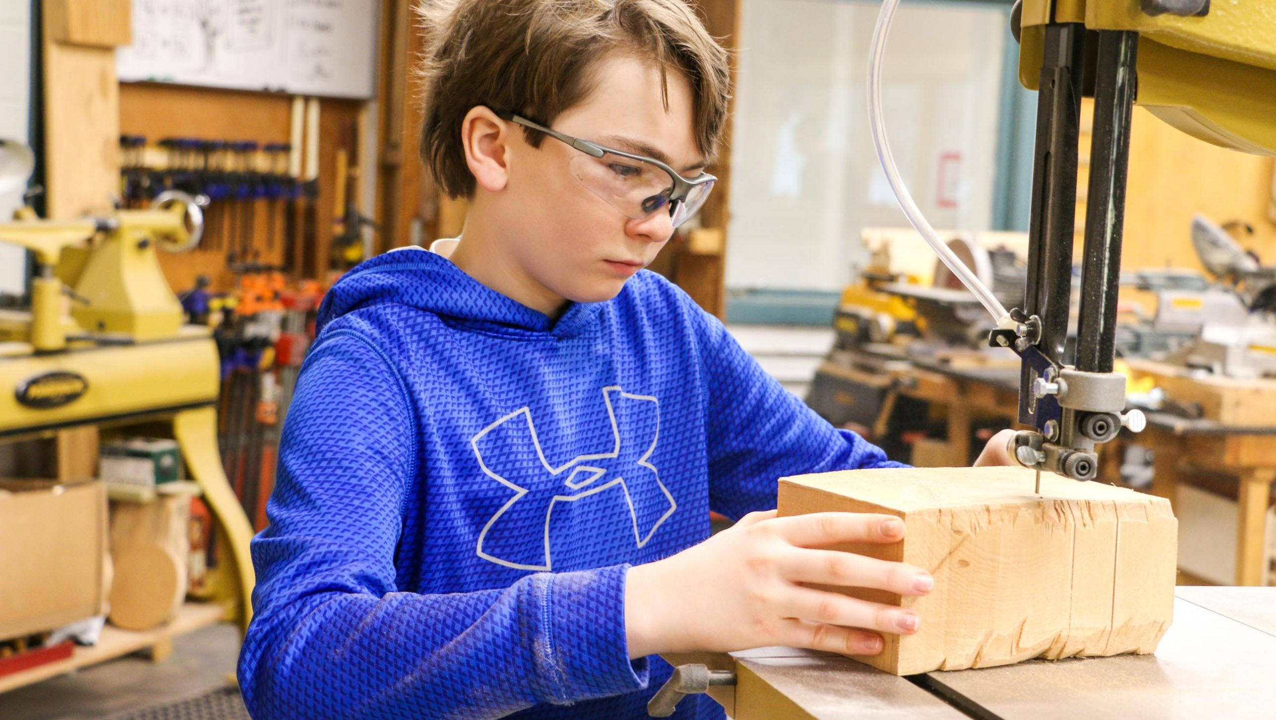 A student cutting a piece of wood using a band saw.