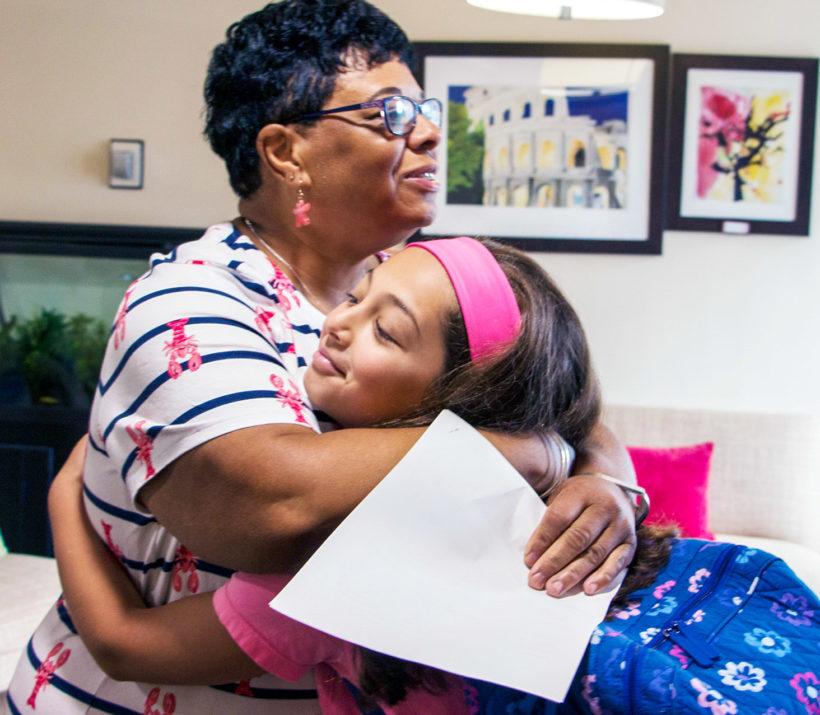 Lynn Mayard hugging a student
