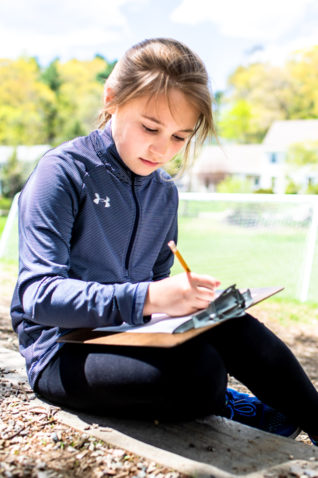 A student sitting outside writing on a clipboard.
