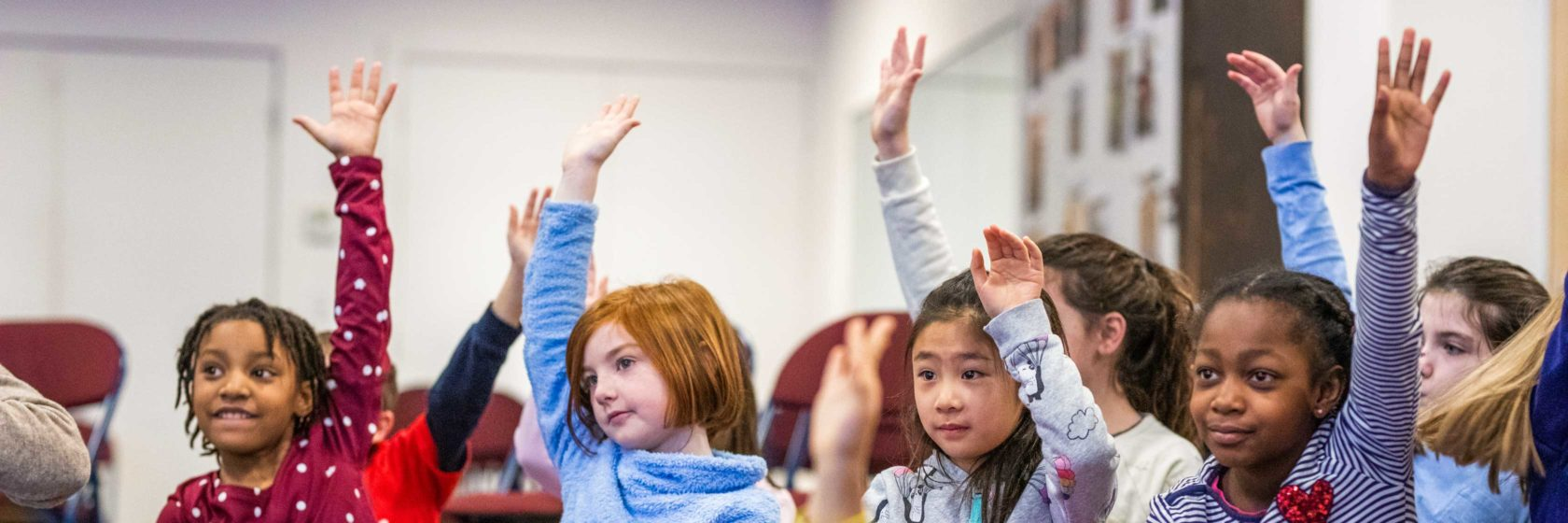 Children raising their hands to ask questions while in class.