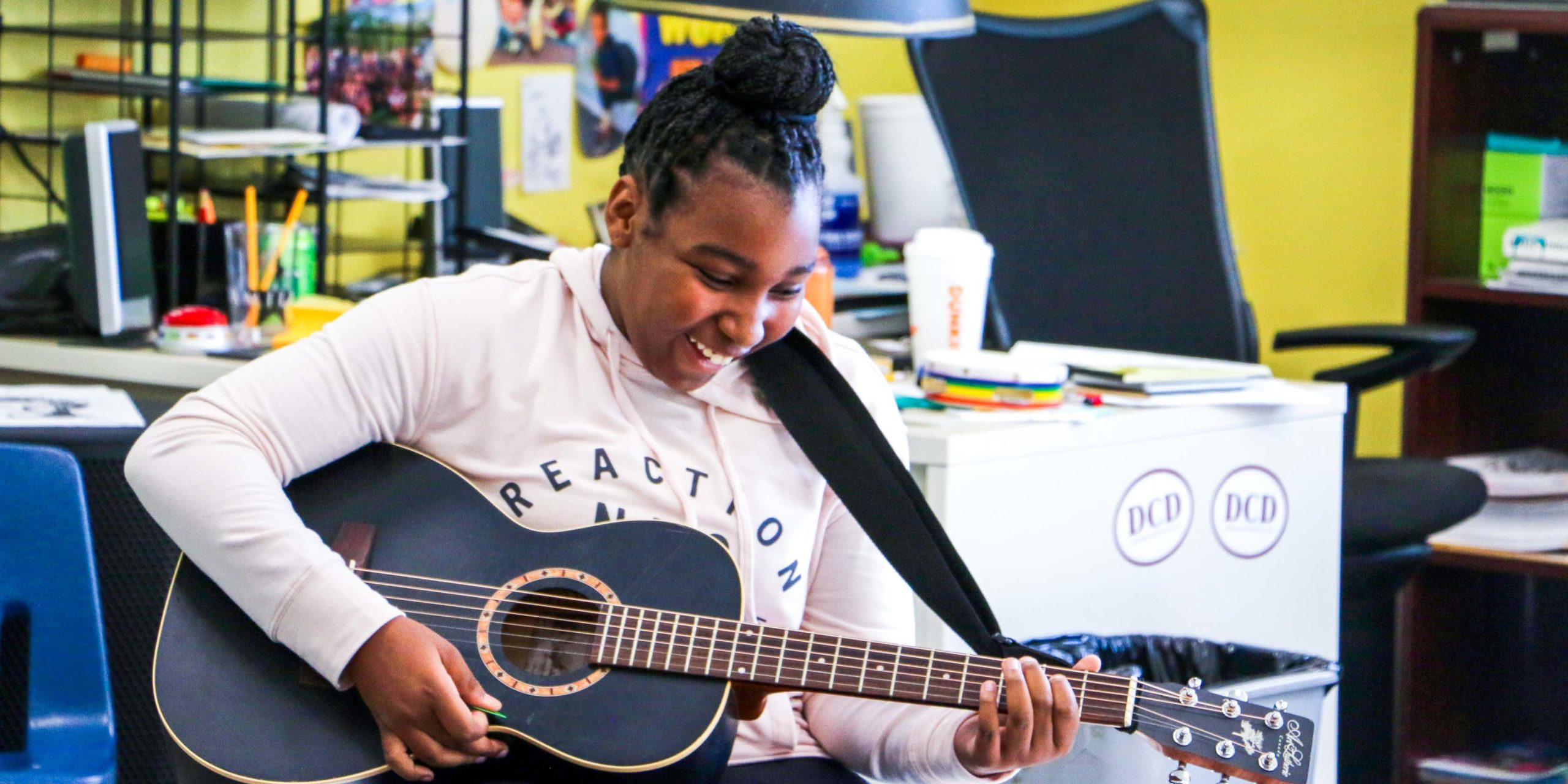 A student playing the guitar and smiling