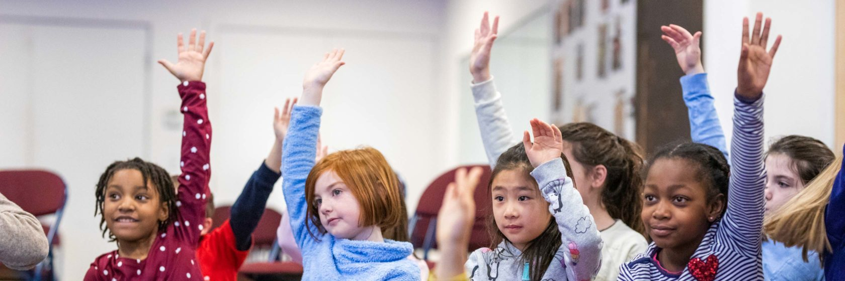 Students raising their hand in a classroom