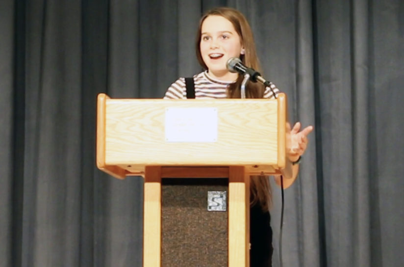 An eighth grader standing at a podium getting ready to speak.