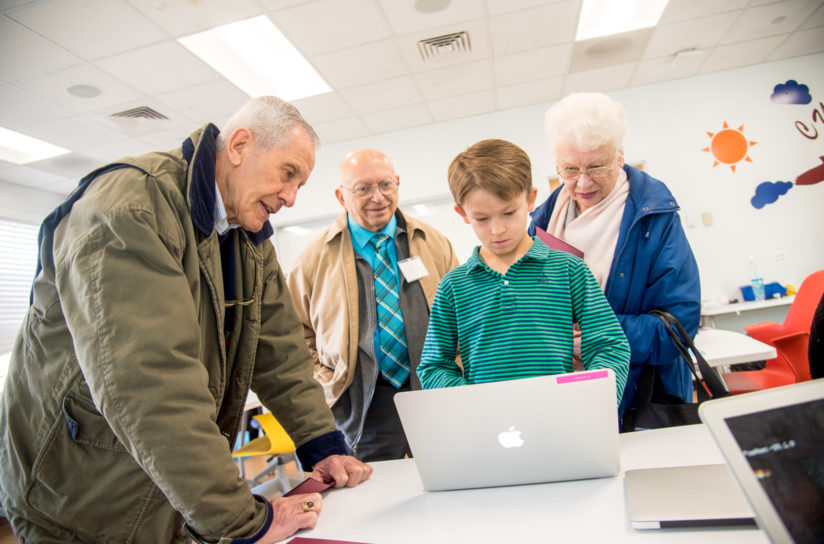 Grandparents watching a student use the computer