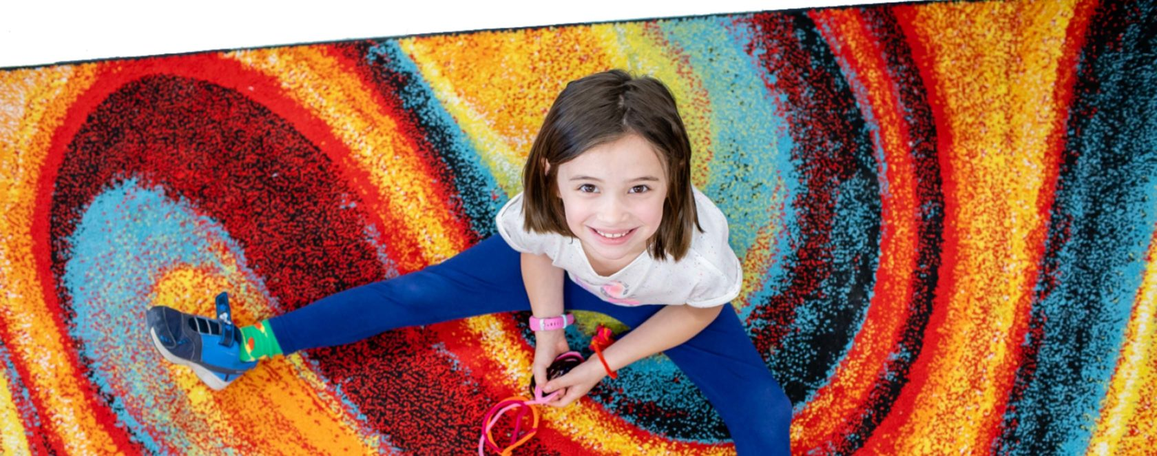 A student sitting on a colorful rug smiling and looking up at the camera.