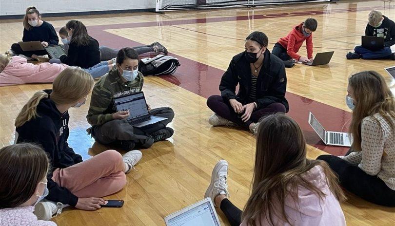 Children sitting on gymnasium floor with laptop computers