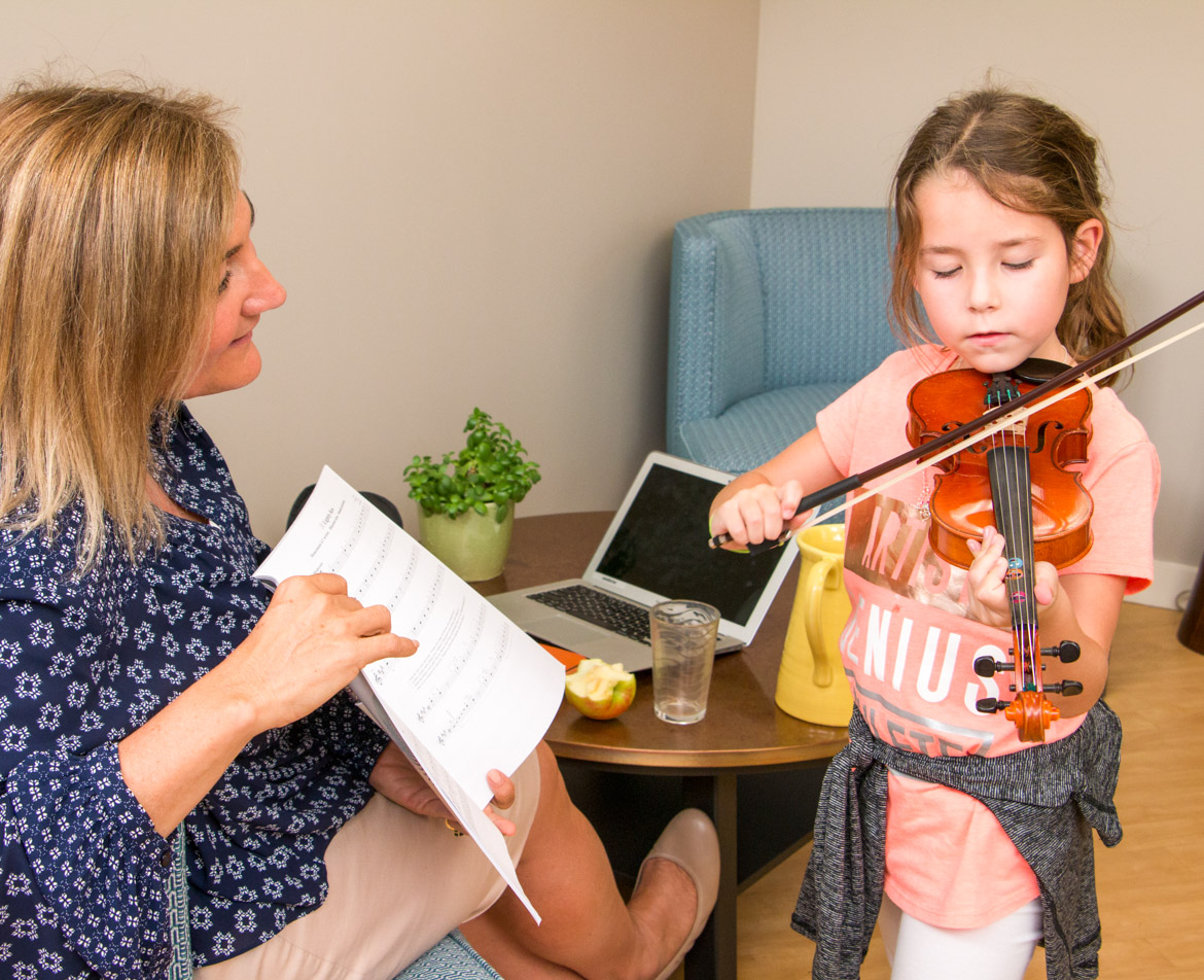 Allison Webster with student playing the violin