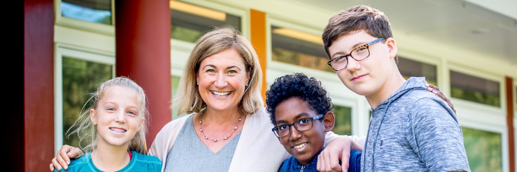 The head of school posing with students