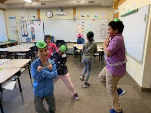 Children representing different ethnicities dancing in the classroom