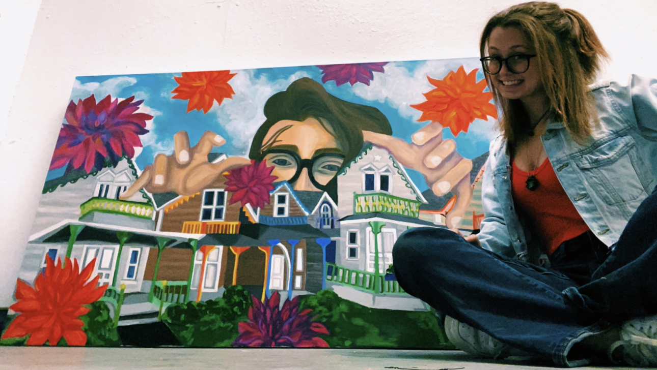 Artist sitting next her painting